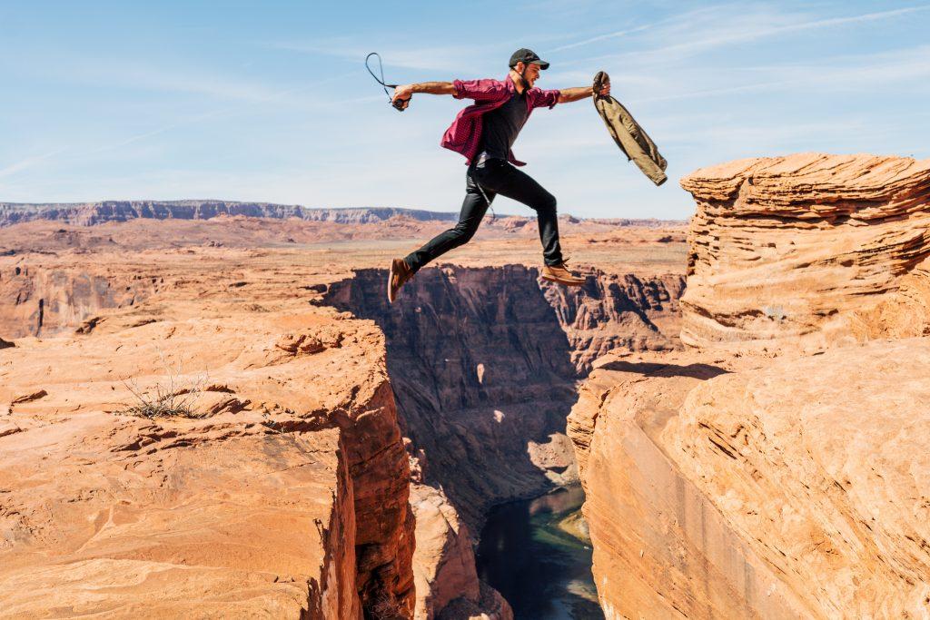 Mann, der hoch über eine tiefe Schlucht springt.